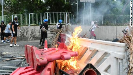 A flight attendant sprints past a burning barricade in Tung Chung on the way to Hong Kong international airport during protests on September 1, 2019.