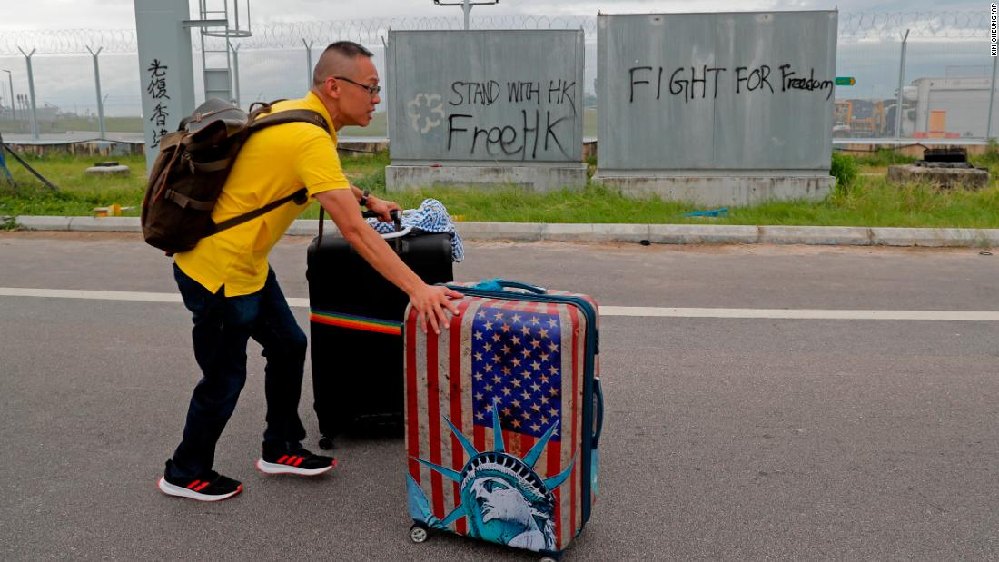 A passenger walks to the airport on September 1 as pro-democracy protesters blocked a road outside the airport.