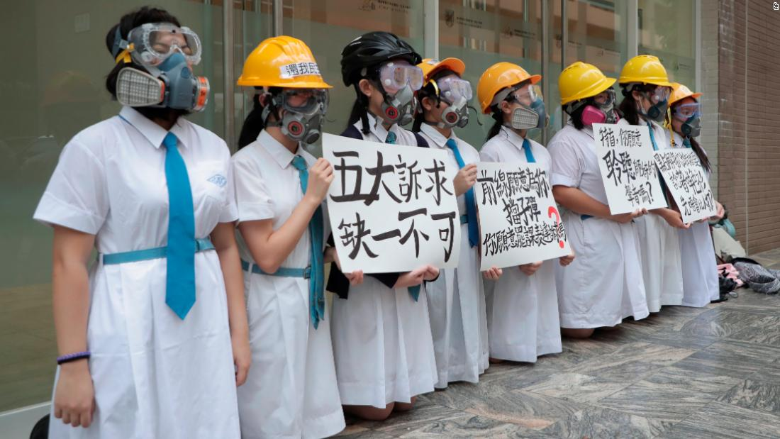 "Students wearing gas masks and helmets hold a banner that reads ""five major demands are indispensable"" at St. Francesco' Canossian College in Hong Kong."