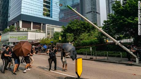 "Protesters attempt to pull down a ""smart"" lamp post during an anti-government rally in Hong Kong on August 24."