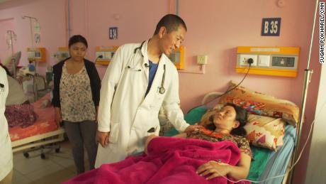 Tshering visits with a patient on hospital rounds.
