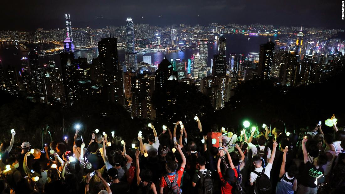 Demonstrators hold up their cell phone lights as they form a human chain at the Peak, a tourist spot in Hong Kong, a settembre 13.