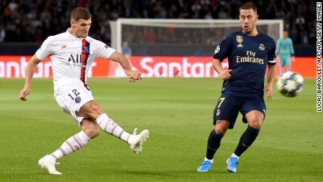 Paris Saint-Germain defender Thomas Meunier (L) challenges Real Madrid's Eden Hazard.