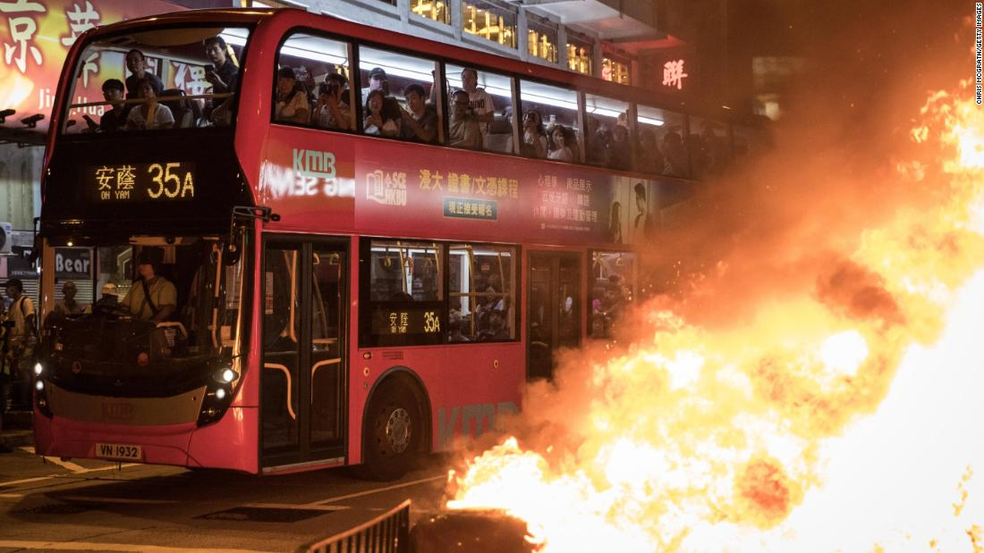Bus passengers look at a burning barricade lit by pro-democracy protesters in front of the Mong Kok police station on Sunday, settembre 22.
