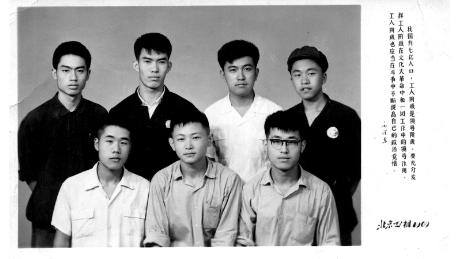 """Xiao (bottom right) and his fellow workers at the Beijing Construction Materials Factory in 1969, during the Cultural Revolution. A Mao quote is printed on the side: """"We must give full play to the leadership role of workers during the Cultural Revolution."""""""