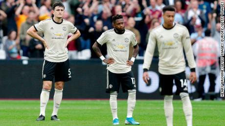 Fred (C) of Manchester United looks dejected with Harry Maguire (L) after West Ham's second goal.