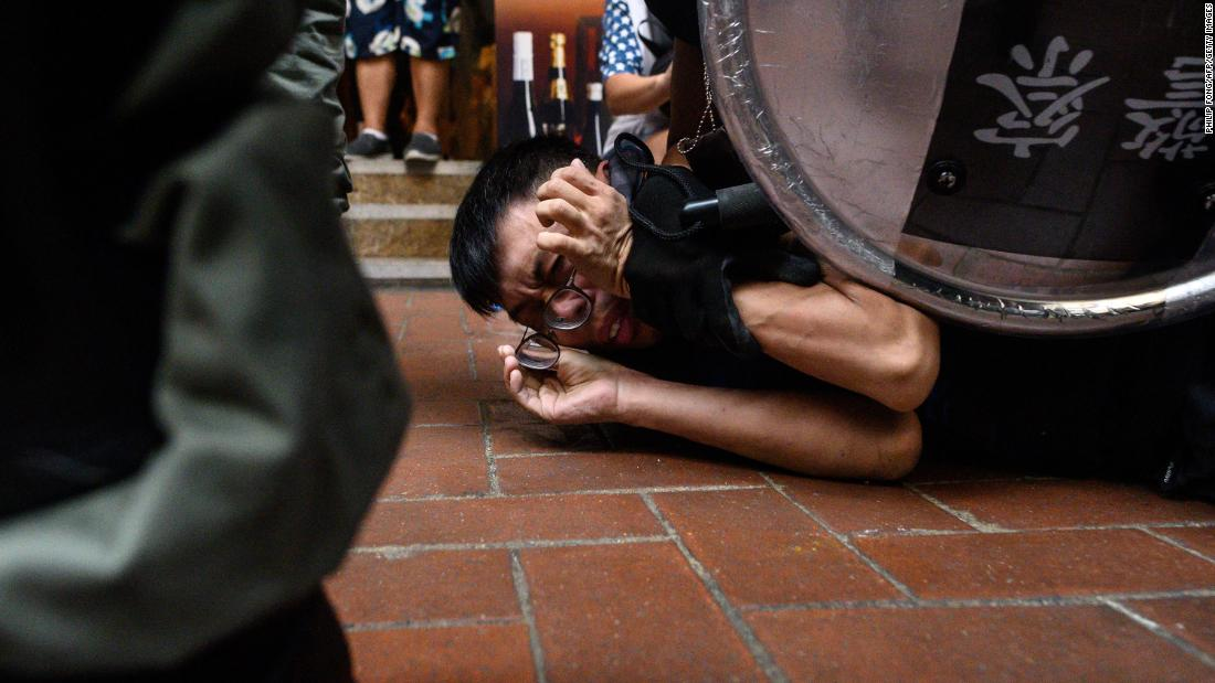 A man is detained by Hong Kong police during a protest in the Causeway Bay shopping district on Sunday, settembre 29.