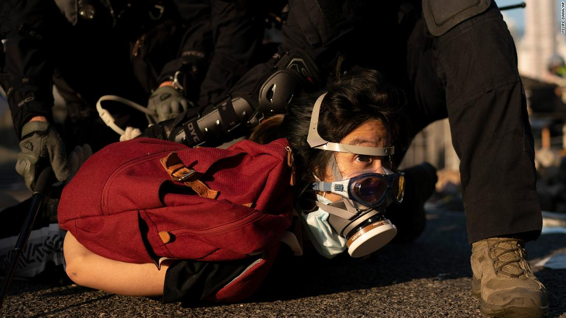 Police detain an anti-government protester on October 1. Thousands of black-clad protesters marched in central Hong Kong as part of multiple pro-democracy rallies.