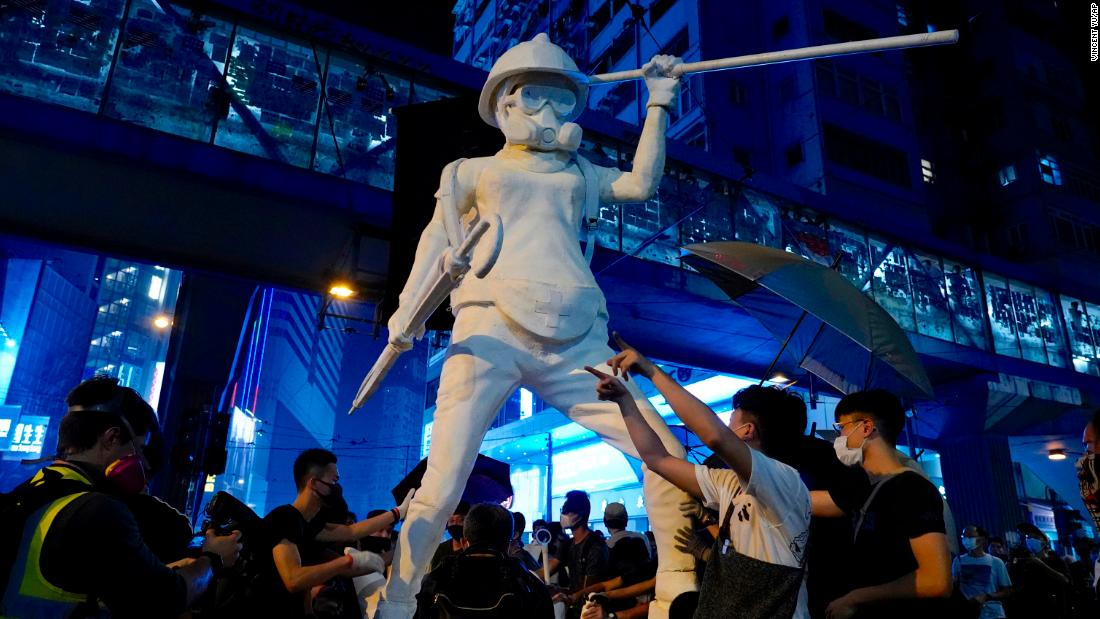 Protesters move a statue depicting a protester armed with gas mask, helmet and umbrella on the streets of Hong Kong on October 4.