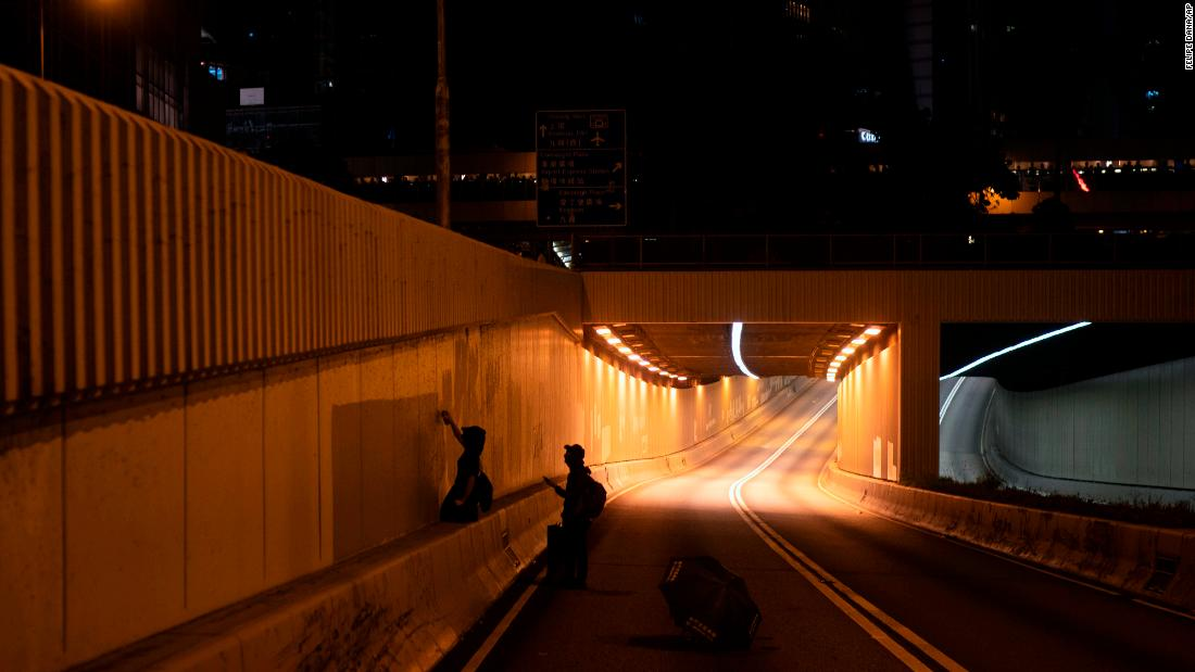 Protesters spray paint slogans at the entrance to a tunnel on October 4.
