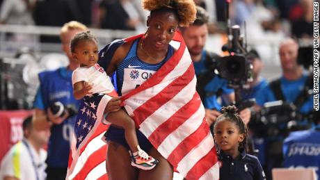 Nia Ali celebrates with her children Yuri (left) and Titus after winning gold in the 100m hurdles in Doha.