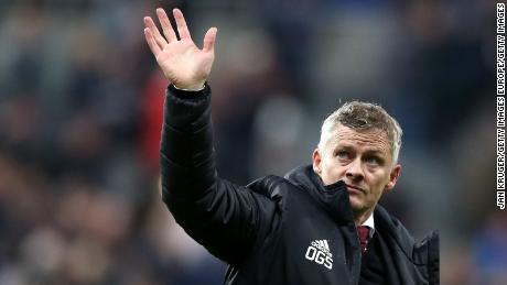 Manchester United coach Ole Gunnar Solskjaer waves to the fans at full-time at Newcastle.