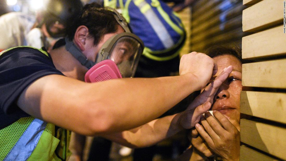 A woman is treated after police fired tear gas to disperse protesters in the Mong Kok district of Hong Kong on October 7.