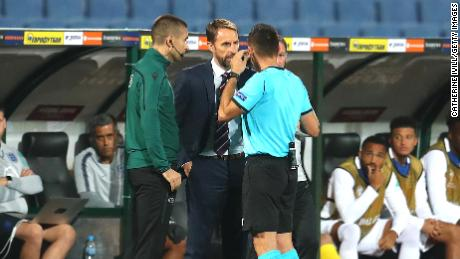 England manager Gareth Southgate speaks with the referee while the game is halted.