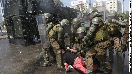 Anti-government demonstrators clash with police as they protest against cost of living increases on October 20 in Santiago, Chile.