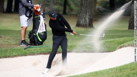 Woods hits out of a bunker on the 11th hole.