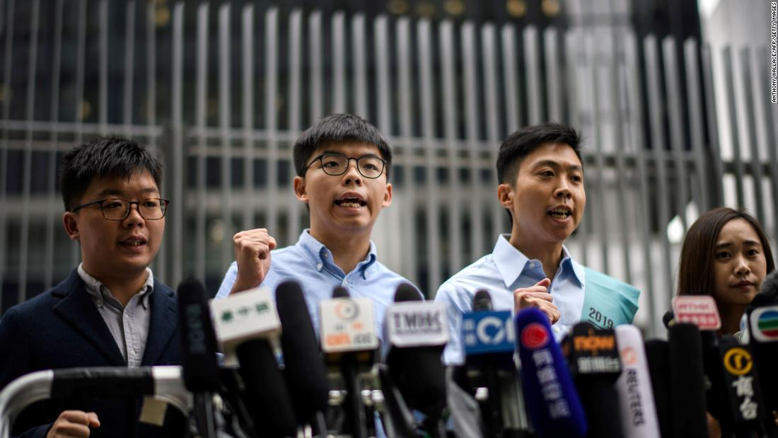 Pro-democracy activist Joshua Wong (second from left) and Kelvin Lam (secondo da destra) shout slogans as they meet the media outside the Legislative Council (LegCo) in Hong Kong on October 29, 2019, after Wong was barred from standing in an upcoming local election.