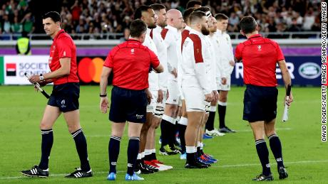 Nigel Owens, the referee, attempts to pull back the England team as they face the New Zealand haka.