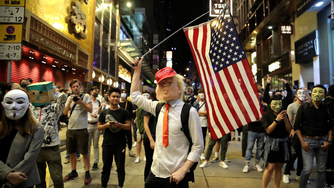 "A person dressed as President Donald Trump waves an American flag on a street in Hong Kong on Thursday, ottobre 31, 2019. Hong Kong authorities braced as pro-democracy protesters urged people on Thursday to celebrate Halloween by wearing masks on a march in defiance of a <a href =""https://www.cnn.com/2019/10/30/asia/halloween-hong-kong-mask-ban-intl-hnk/index.html"" target =""_blank&ampquott;>government ban on face coverings</un>."
