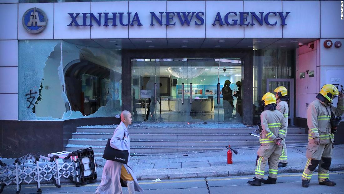 Firefighters stand outside the offices of China's Xinhua News Agency after its windows were damaged by protesters in Hong Kong on Saturday, novembre 2. Hong Kong riot police fired multiple rounds of tear gas and used a water cannon Saturday to break up a rally by thousands of masked protesters demanding autonomy after Beijing indicated it could tighten its grip on the Chinese territory.