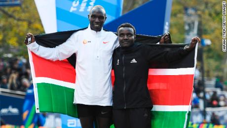 Geoffrey Kamworor and Joyciline Jepkosgei pose with the Kenya flag after the New York Marathon.