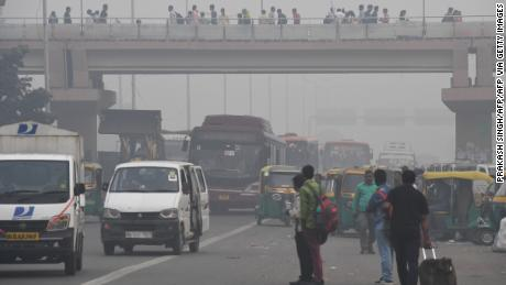People make their way on a street in smoggy conditions in New Delhi on November 4, 2019.