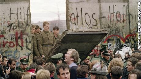 West Berliners crowded in front of the Berlin Wall on November 11 1989, watching East German border guards demolishing a section of the barrier.