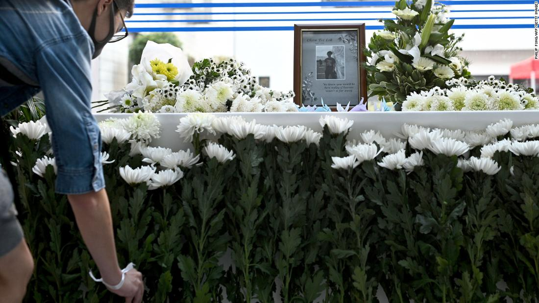 A person places a flower at a memorial for 22-year-old Hong Kong university student Chow Tsz-lok on November 8.