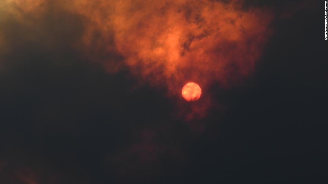 The sun is seen through heavy smoke as a bushfire burns in Woodford.