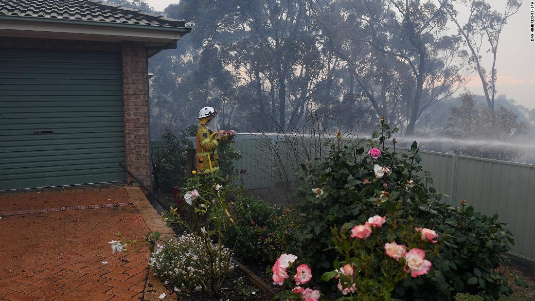 Firefighters hose down an area in Woodford.