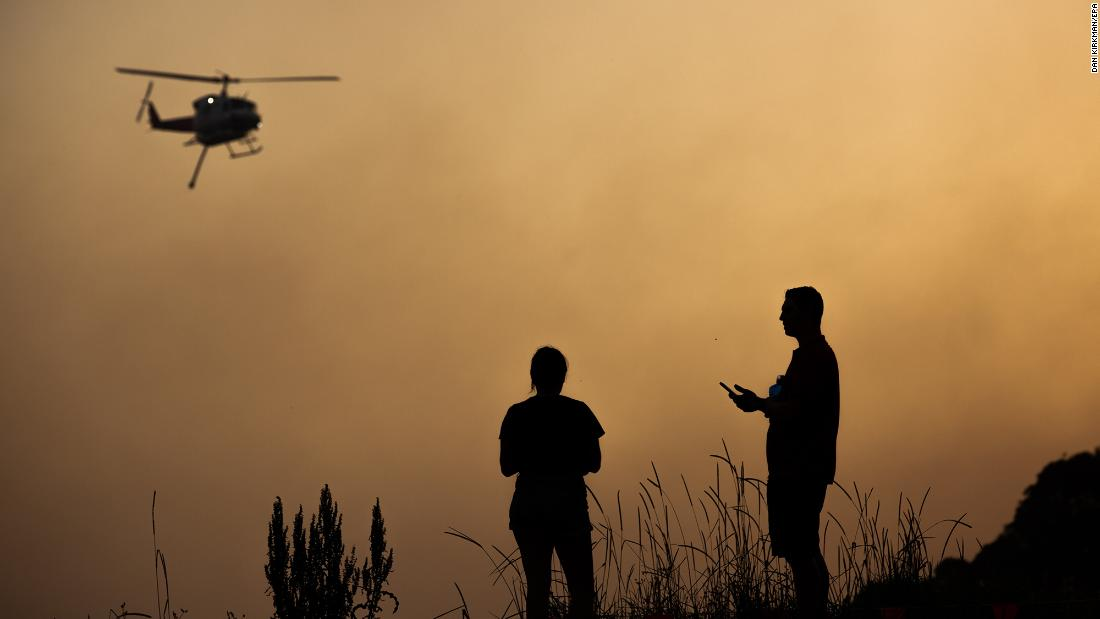 Forster residents watch as a water-bombing helicopter flies over a bushfire on November 7.