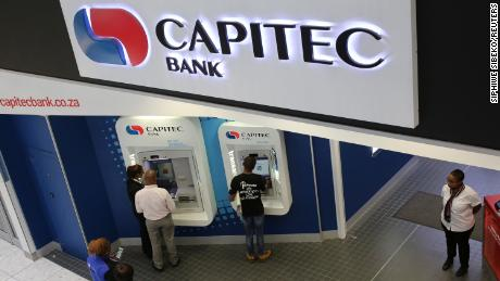 Customers draw money from an ATM outside a branch of Capitec Bank in Johannesburg.