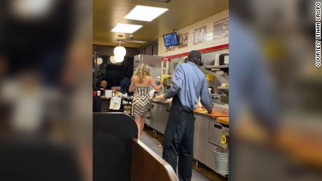 After a night out, a woman in heels saw to clearing tables and stacking cups.
