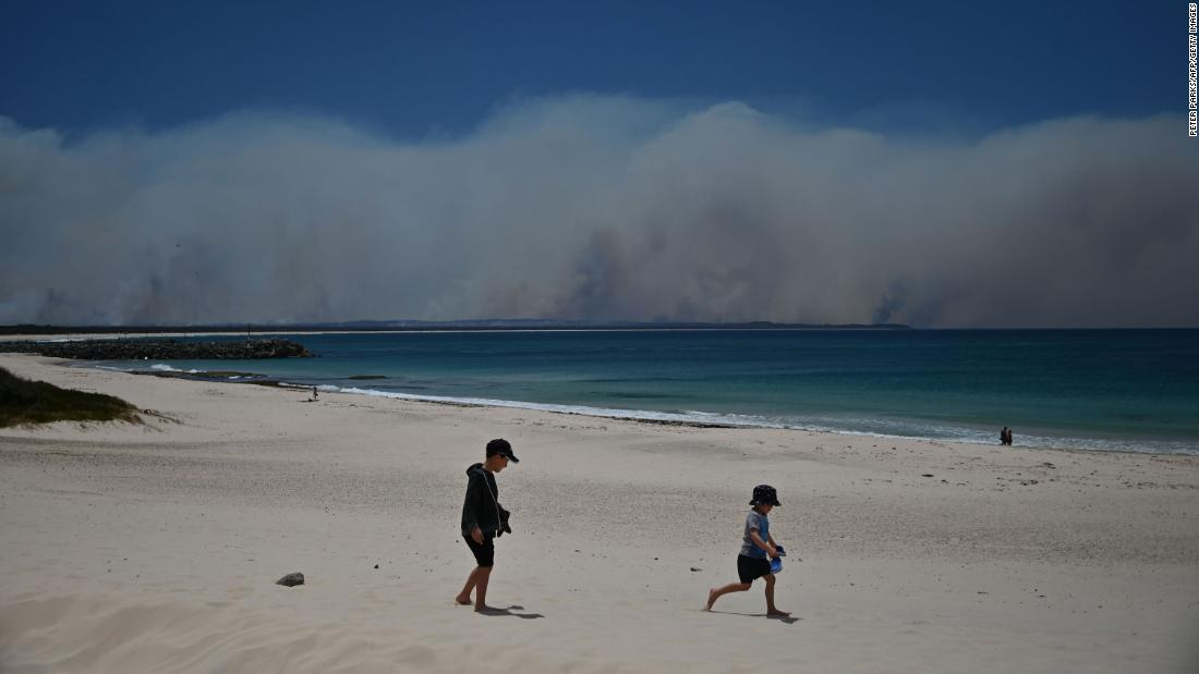 Fires burn in the distance as children play on a beach in Forster on November 9.