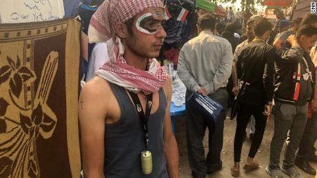 Un manifestante en la ciudad de la tienda de campaña le pintó la bandera iraquí en la cara. Lleva una lata de gas lacrimógeno como medalla para mostrar que no tiene miedo.