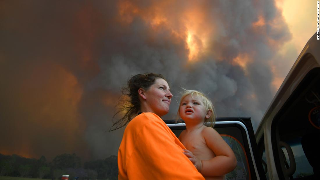 Residents look on as thick smoke rises from bushfires near Nana Glen on November 12.