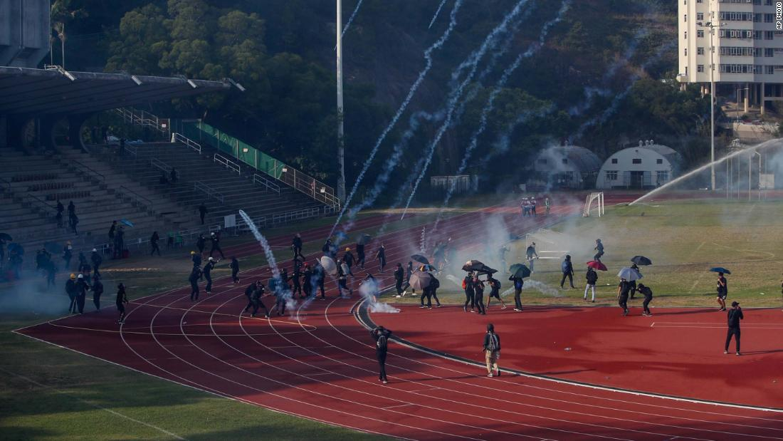 Students attempt to clear tear gas canisters fired by riot police onto a sports track during a confrontation at the Chinese University in Hong Kong on Tuesday, novembre 12.