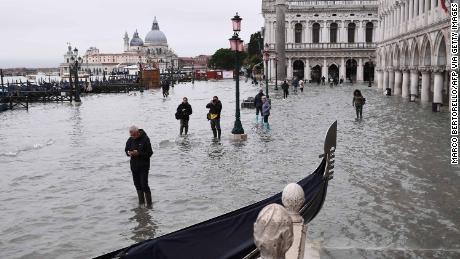 People walk past a stranded gondola across the flooded Riva degli Schiavoni embankment and St. Mark's Square in the background.