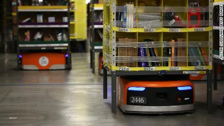 Robots move shelves of merchandise at an Amazon fulfillment center.