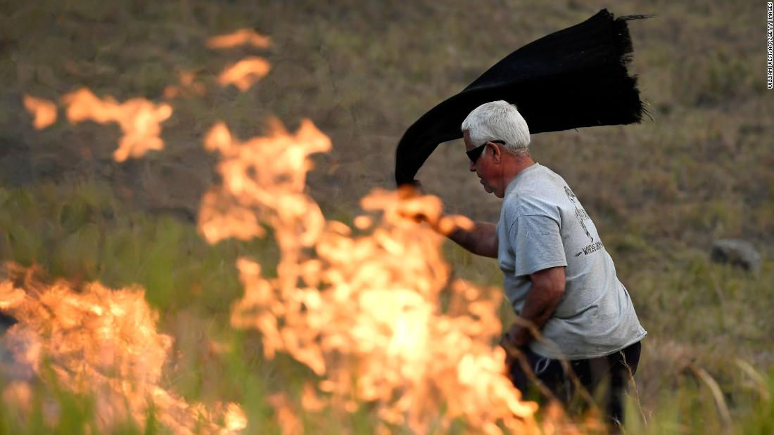 A man uses a wet towel to help put out flames near the town of Taree on November 14.