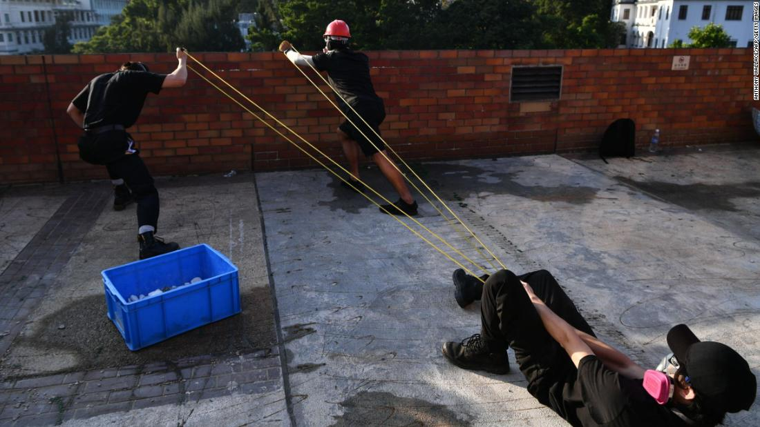 Protesters use a catapult to fire bricks at the police from inside the Hong Kong Polytechnic University on November 17.