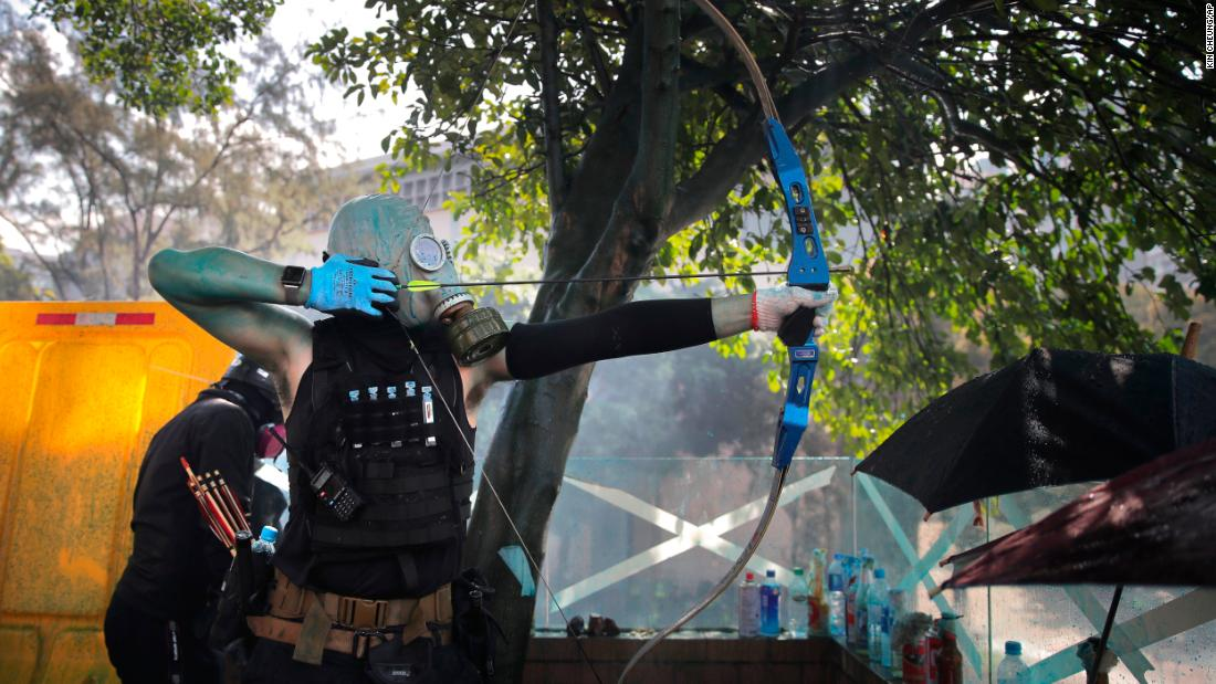 A protester prepares to shoot an arrow during a confrontation with police.
