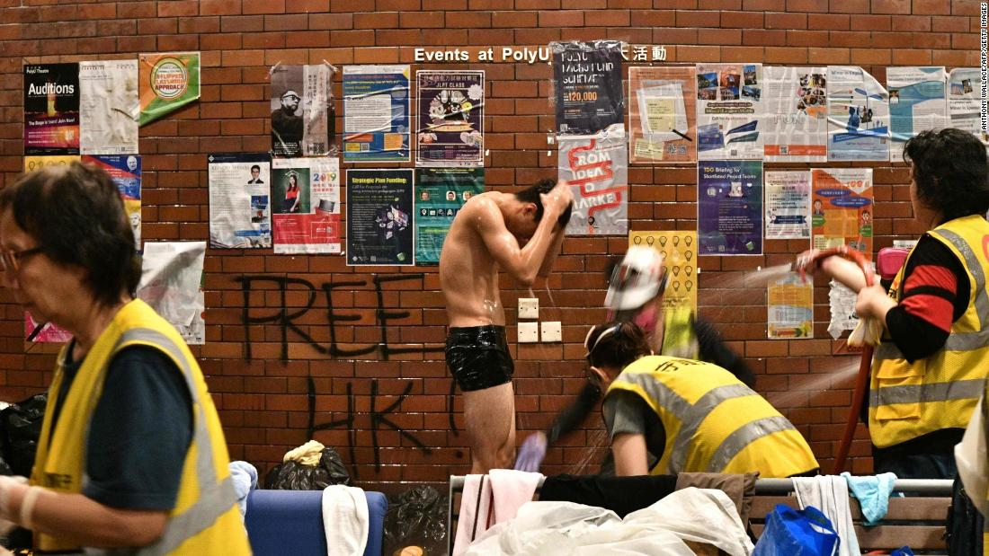 An anti-government protester is showered down by volunteer medical workers after he was soaked by a police water cannons firing pepper spray-infused water at Hong Kong Polytechnic University on November 18.