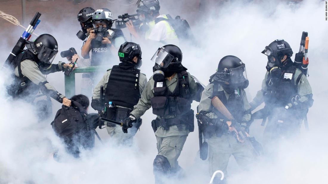 "Police in riot gear move through a cloud of smoke as they detain a protester at the Hong Kong Polytechnic University in Hong Kong on November 18. Police have <a href =""https://edition.cnn.com/asia/live-news/hong-kong-protests-live-nov-18-intl-hnk/index.html"" target =""_blank&ampquott;>attempted to clear the university</un>, which has been occupied by protesters for days as a strategic protest base."