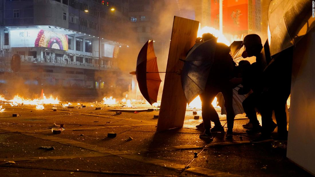 Protesters react as police fire tear gas in the Kowloon area of Hong Kong, Lunedi, novembre 18.