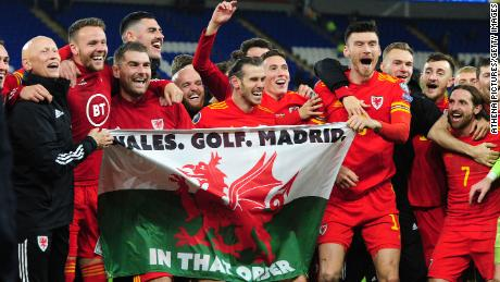 """Wales celebrate with the infamous """"Wales. Golf. Madrid flag."""""""