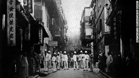 Plague inspectors on a street of Hong Kong, around 1890.