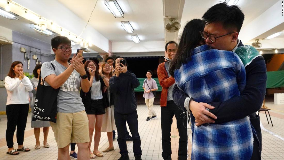 Pro-democracy candidate James Yu hugs his girlfriend after winning his seat in district council elections, early November 25.