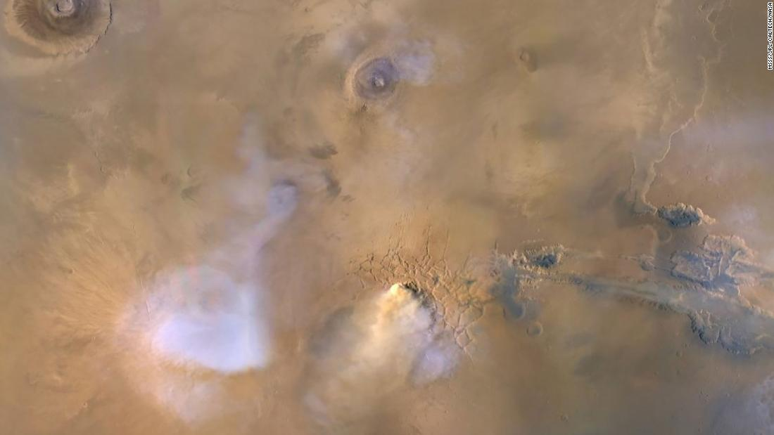 The cloud in the center of this image is actually a dust tower that occurred in 2010 and was captured by the Mars Reconnaissance Orbiter. The blue and white clouds are water vapor.