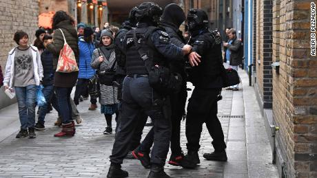 Police apprehend a man in a street on the south side of London Bridge.
